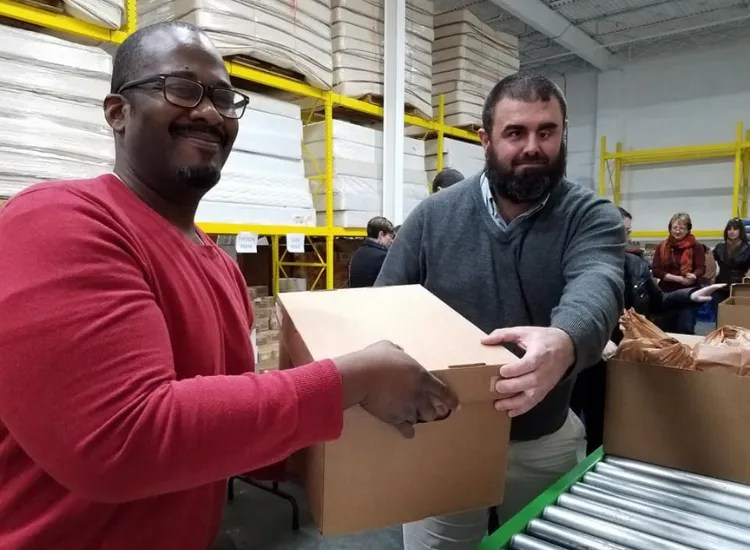 Two men hold a box in a warehouse.
