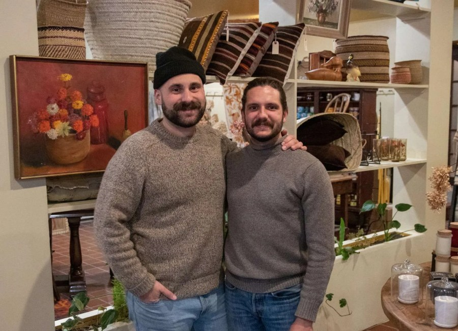Ben and Blake of Village Common in Catskill stand in front of a display of home goods in their store.