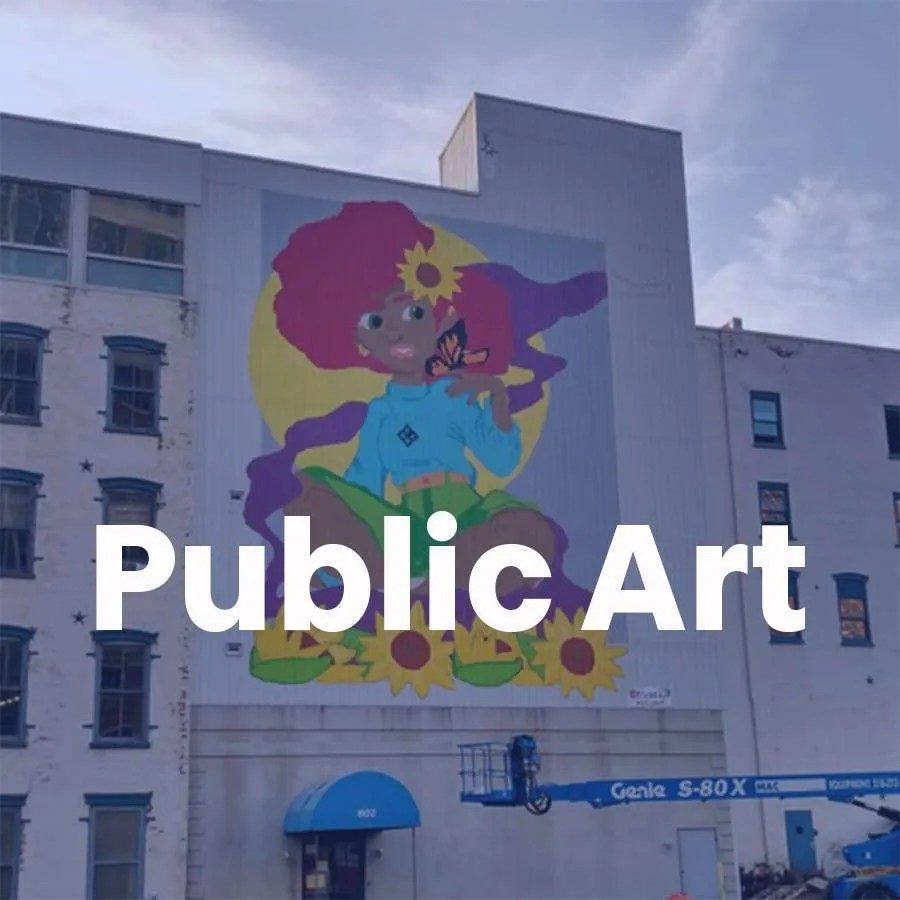 Bright colorful painting of a girl on a building wall that acts as a link to the page for Public ARt.