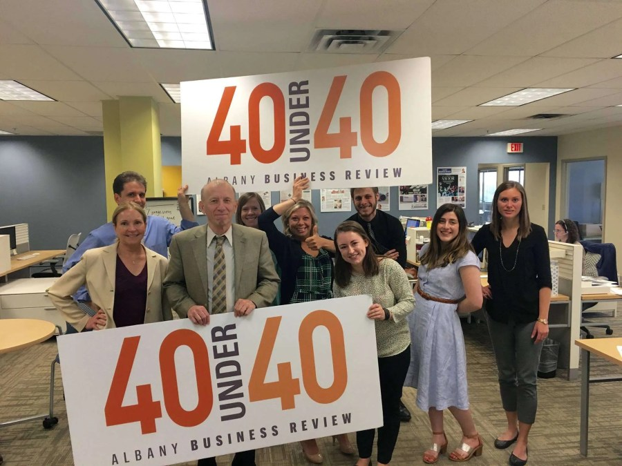 A group of people are holding up signs that say 40 Under 40 - Albany Business Review.