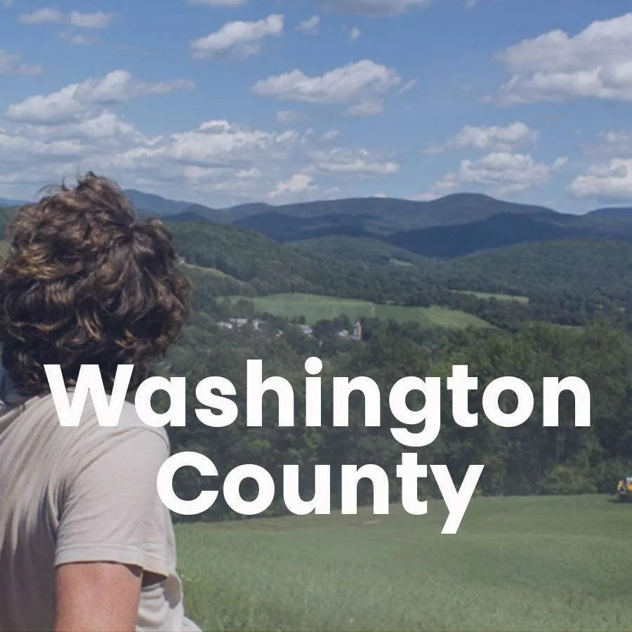 """Photo of the back of a person looking over the foothills of the Adirondacks with a super across the photo that says """"Washington County"""""""
