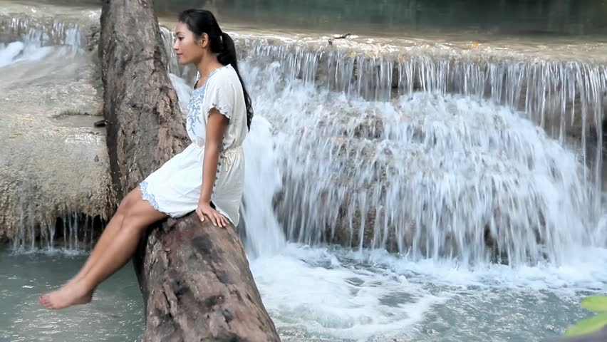 Contemplating in nature near waterfall