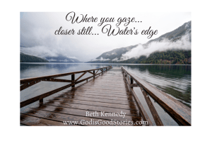 A long wooden jetty heading out into a lake of still waters with mist and mountains with words, where you gaze, closer still, water's edge Beth Kennedy www.GodisGoodStories.com