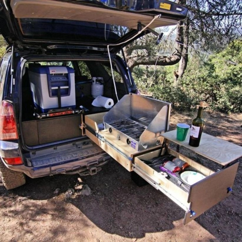 Suv camper has a bed frame with an abundance of storage underneath, a kitchen unit with a sink, many handy places for extra storage, a back-up camera, and much more
