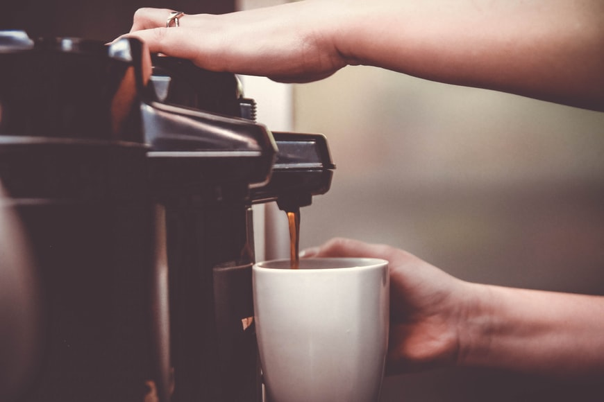 Person Pouring Coffee from a Coffee Machine