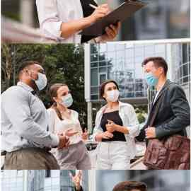 Colleagues chat outdoors during pandemic with face masks Free Download