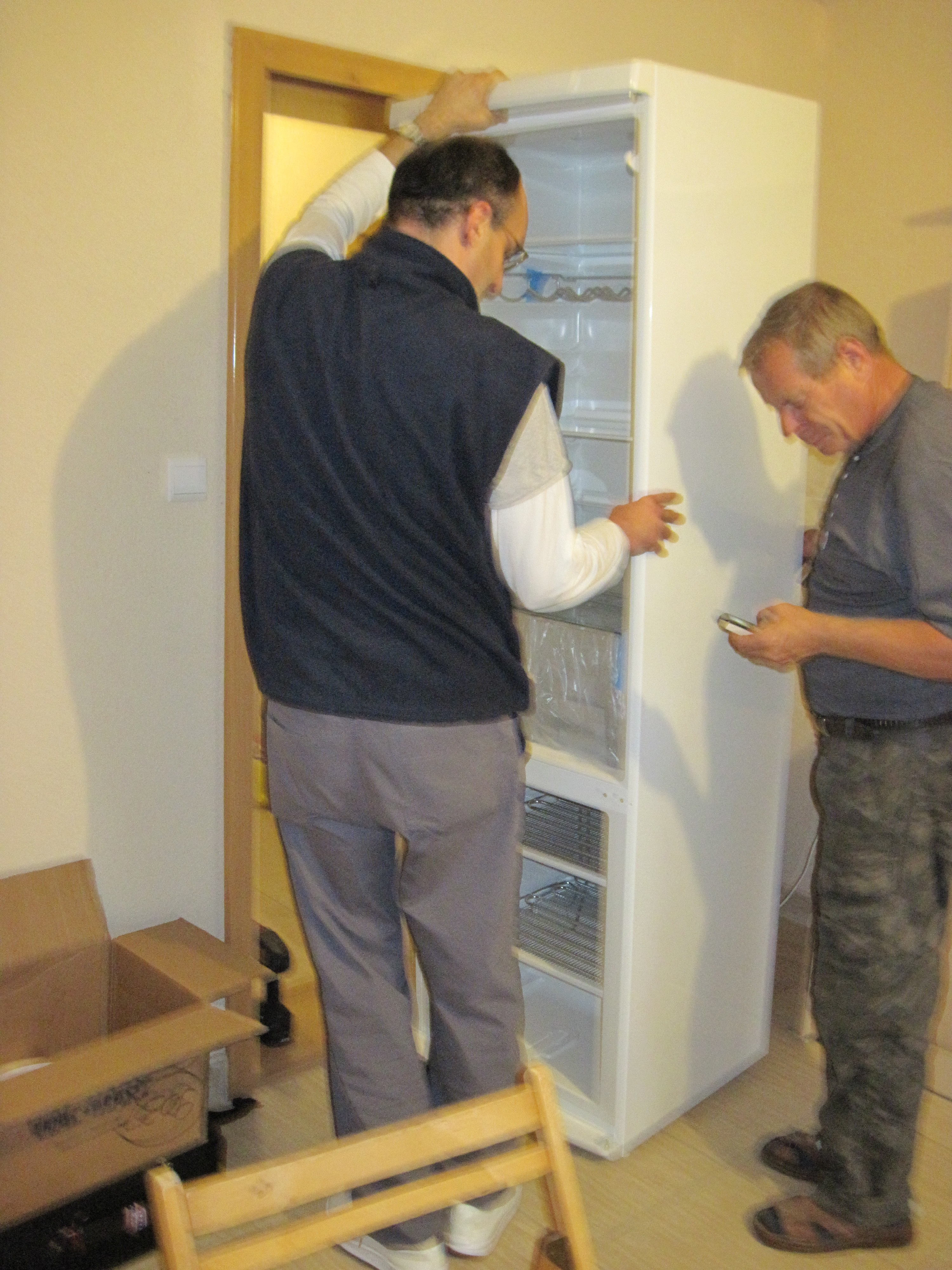 Tibi and Gusti had to remove the fridge door in order to move it so I can easily open the door.  The delivery men somehow got it in place but then the fridge door, and the kitchen door hit each other!  The men moved it across the room for me.