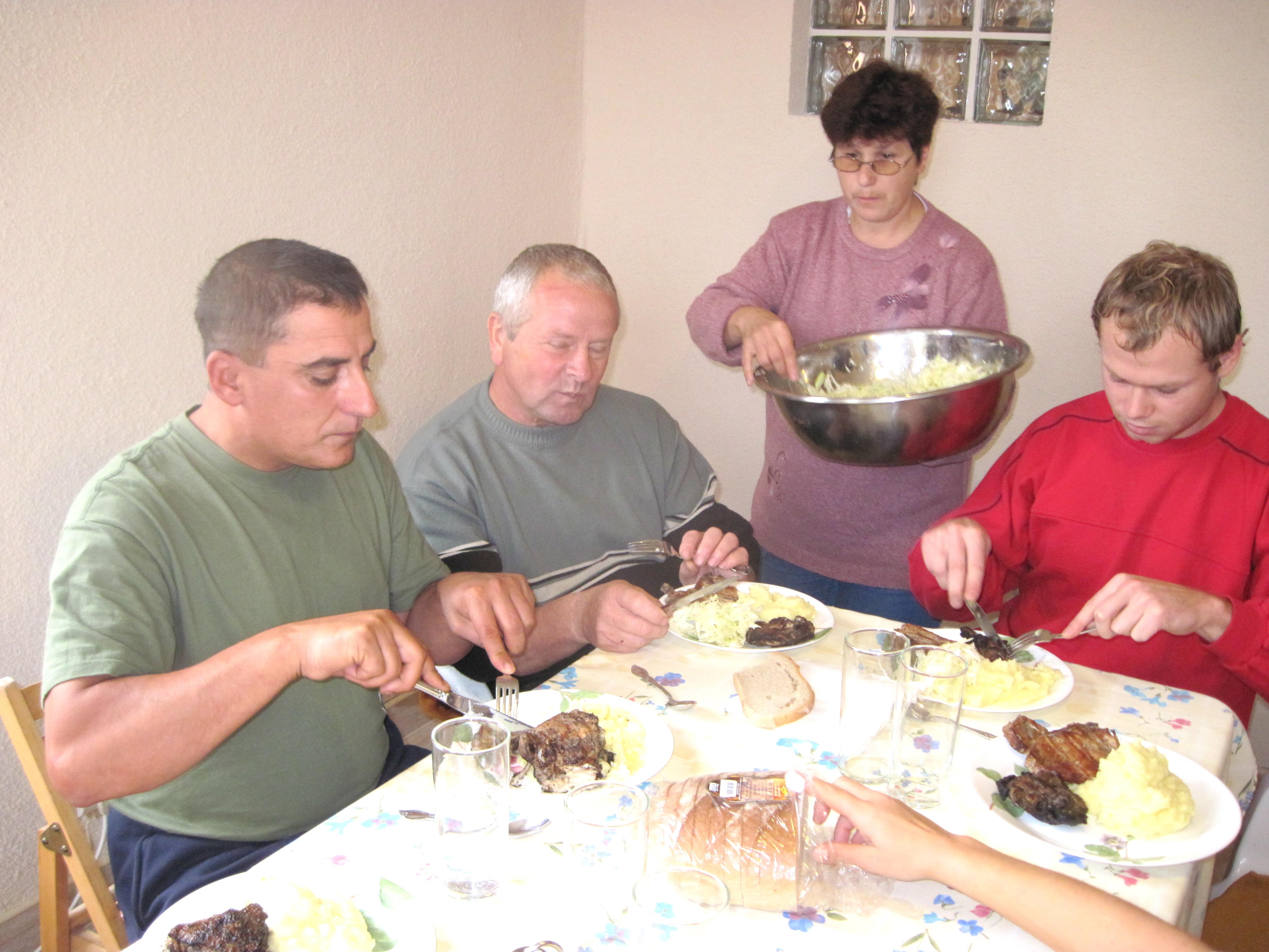 Sebastian, Vasili & Marti let Mimi serve them some slaw.  (Sebastian grilled the meat outdoors in the rain!)
