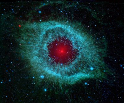 This infrared image from NASA's Spitzer Space Telescope shows the Helix nebula, a cosmic starlet often photographed by amateur astronomers for its vivid colors and eerie resemblance to a giant eye. The nebula, located about 700 light-years away in the constellation Aquarius, belongs to a class of objects called planetary nebulae. Discovered in the 18th century, these cosmic butterflies were named for their resemblance to gas-giant planets. Planetary nebulae are actually the remains of stars that once looked a lot like our sun. When sun-like stars die, they puff out their outer gaseous layers. These layers are heated by the hot core of the dead star, called a white dwarf, and shine with infrared and visible-light colors. Our own sun will blossom into a planetary nebula when it dies in about five billion years. In Spitzer's infrared view of the Helix nebula, the eye looks more like that of a green monster's. Infrared light from the outer gaseous layers is represented in blues and greens. The white dwarf is visible as a tiny white dot in the center of the picture. The red color in the middle of the eye denotes the final layers of gas blown out when the star died. The brighter red circle in the very center is the glow of a dusty disk circling the white dwarf (the disk itself is too small to be resolved). This dust, discovered by Spitzer's infrared heat-seeking vision, was most likely kicked up by comets that survived the death of their star. Before the star died, its comets and possibly planets would have orbited the star in an orderly fashion. But when the star blew off its outer layers, the icy bodies and outer planets would have been tossed about and into each other, resulting in an ongoing cosmic dust storm. Any inner planets in the system would have burned up or been swallowed as their dying star expanded. The Helix nebula is one of only a few dead-star systems in which evidence for comet survivors has been found. This image is made up of data from Spi