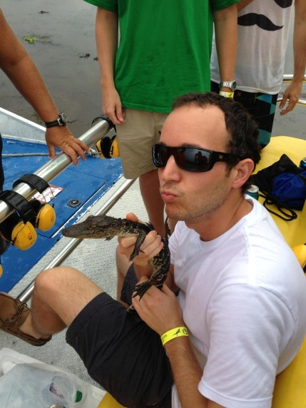 Math teacher Bryan Cole holding an alligator in the Louisiana Bayou.