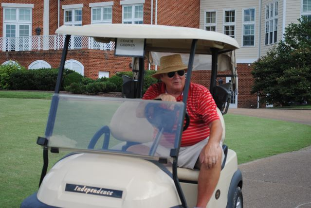 Golf coach Tom Hoy rides in golf cart during tournament.