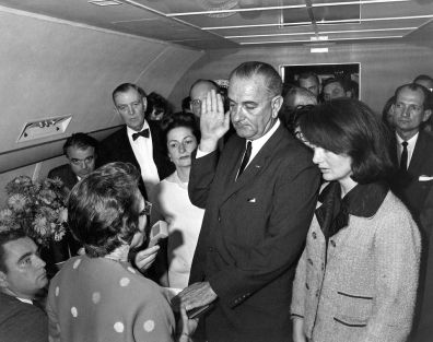 Jackie Kennedy on Air Force One swearing in Lyndon Johnson, still wearing her pink suit stained with her husband's blood.