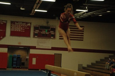 Senior McKaella Grow doing a jump series on beam.
