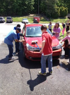 Owen Hicks, Katie Stoyanoff, Desmond Ntumy, and AJ Pleasants working hard on cleaning a car.