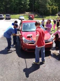 Owen Hicks, Katie Stoyanoff, Desmond Ntumy, and AJ Pleasants working hard on cleaning a car.