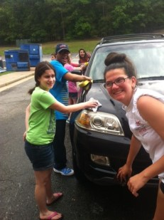 Sarah Platea, AJ Pleasants, and Madison Beale grin while washing a car.