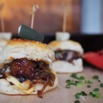 Give Meatball Sliders a Southern twist with this easy appetizer recipe perfect for game night! Rosina Artisan Smoky Maple Bacon Meatballs are tossed in sweet spicy BBQ sauce, topped with melted cheddar cheese, sautéed caramelized onions, and extra crispy bacon (because we all love bacon!) then sandwiched between fluffy buttermilk biscuits. We are taking BBQ Meatball Sliders to the next level! Recipe by GoEpicurista.com using frozen meatballs, frozen biscuits and ready made BBQ sauce.