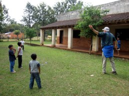 Dad playing frisbee with the kids at the soup kitchen