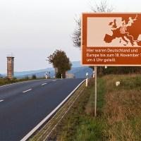 Erinnerungstafel an den früheren deutsch-deutschen Grenzverlauf vor dem Hintergrund eines Beobachtungsturms der Grenzsicherungsanlagen der DDR