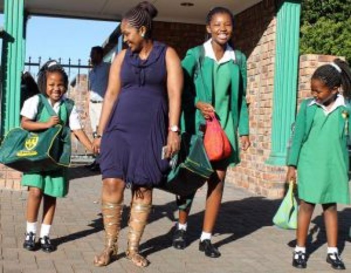 Caption for image : EDUCATION FIRST: Parents of schoolgoing children have started moving closer to top schools, packing up where they live and buying homes in suburban areas in East London. Entle Booi was all smiles on her first day at Stirling Primary School, accompanied by her mother, Viwe, and older sisters Vuyisa and Anda in this file photo Picture: SARAH KINGON