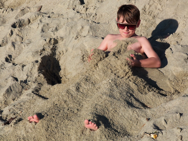 boy buried in sand on the beach, california