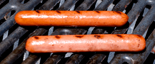 hot dogs frankfurters bbq cooking on a grill