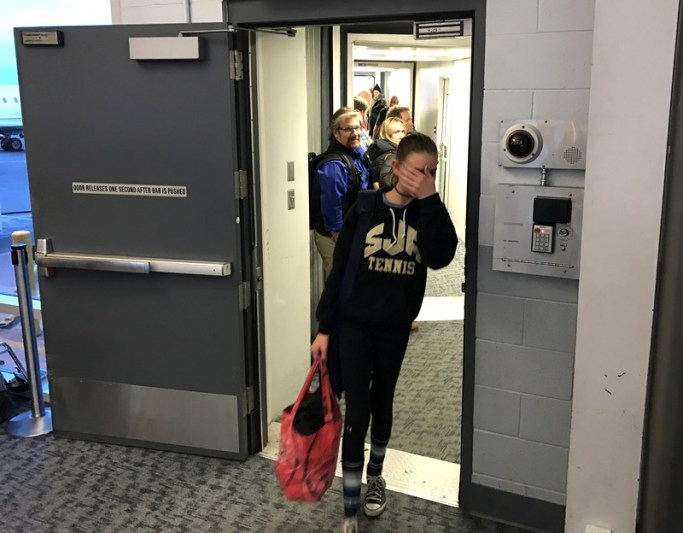 young girl coming off airplane plane gate corridor dia