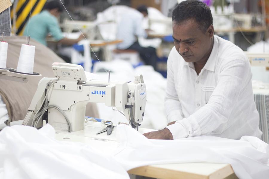 man sewing sheets, india