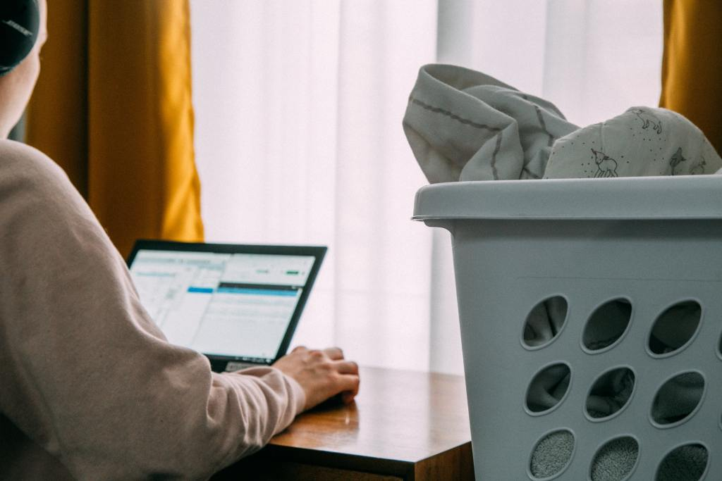 Image of person in grey hoodie working on laptop next to laundry basket