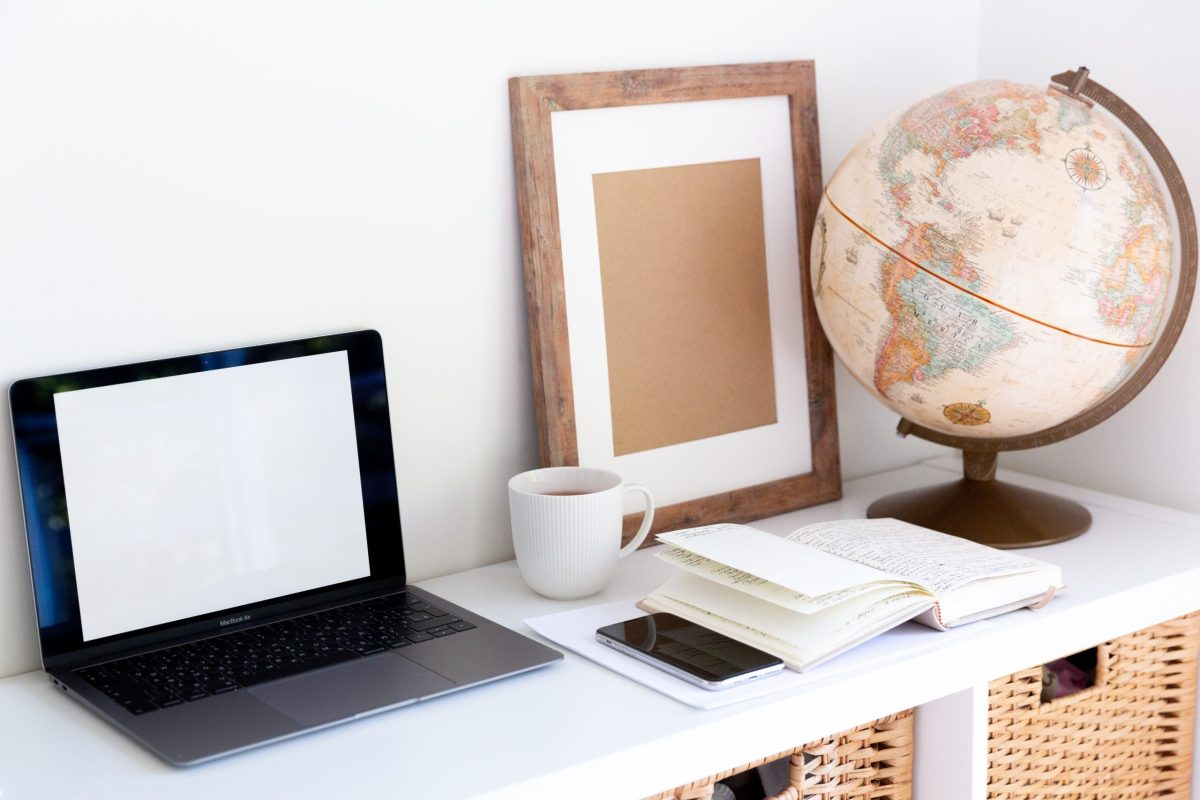 laptop next to a smartphone and a globe
