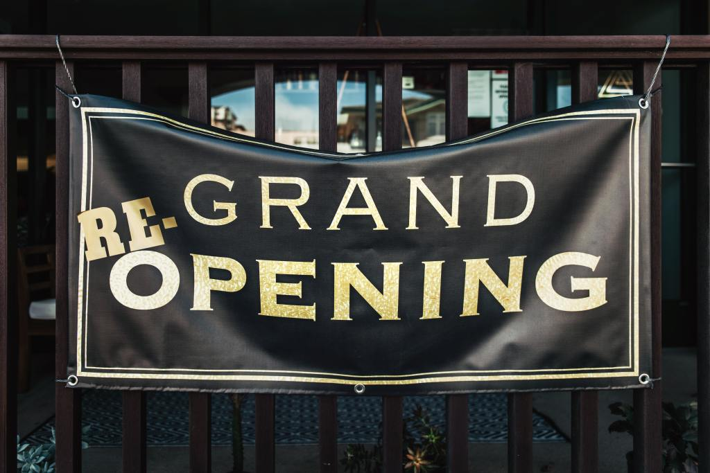 """black banner with """"grand re-opening"""" printed on it in gold uppercase letters."""