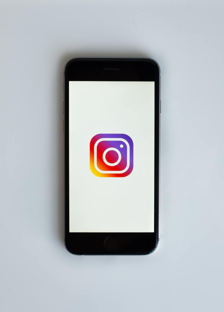 A black iPhone laying on a white surface, displaying the Instagram logo on a white background.