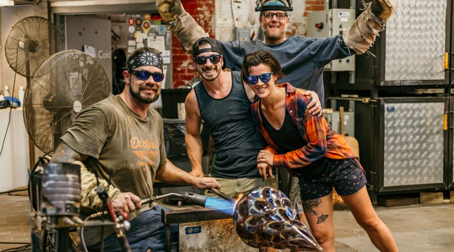 Dan Alexander sitting down in the hot glass studio, torching a large glass work, surrounded by two friends, with Scott Krenitsky, hot glass studio manager raising his arms in victory in the background. All are smiling for the photo.