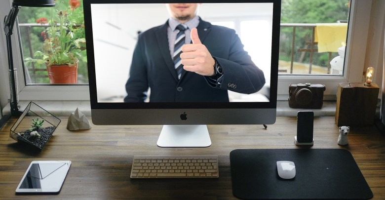 A man showing a thumb up in an online meeting symbolizing how to succeed in your next virtual interview.