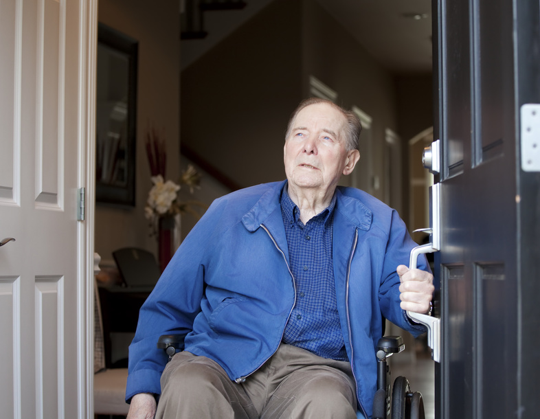 Elderly man in wheelchair at his front door, looking up