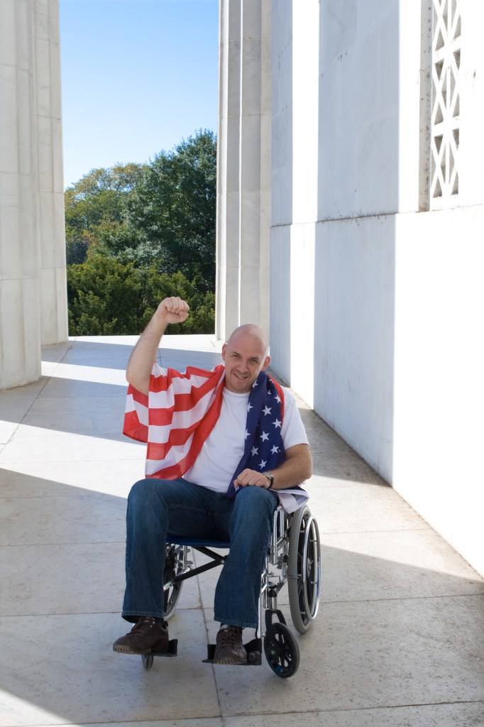 Patriotic white man sitting in a wheelchair with raised fist and American flag draped across his shoulders. Shot at the Lincoln Memorial, in Washington, DC, USA.