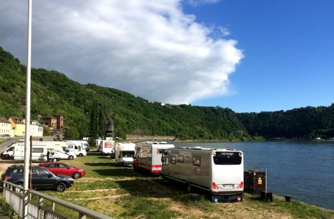 Große Wohnmobile stehen direkt am Rheinufer, im Hintergrund der Loreleyfelsen