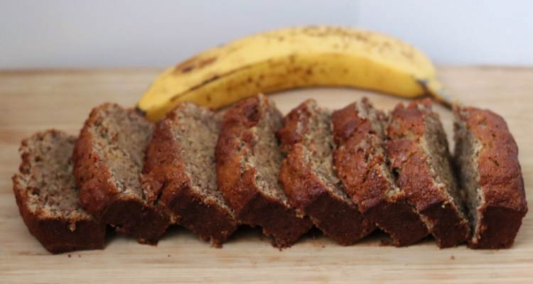 Banana bread on a wooden board and a banana in the background