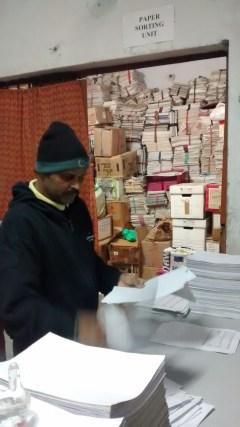 Goonj staff, segregating one side printed paper.