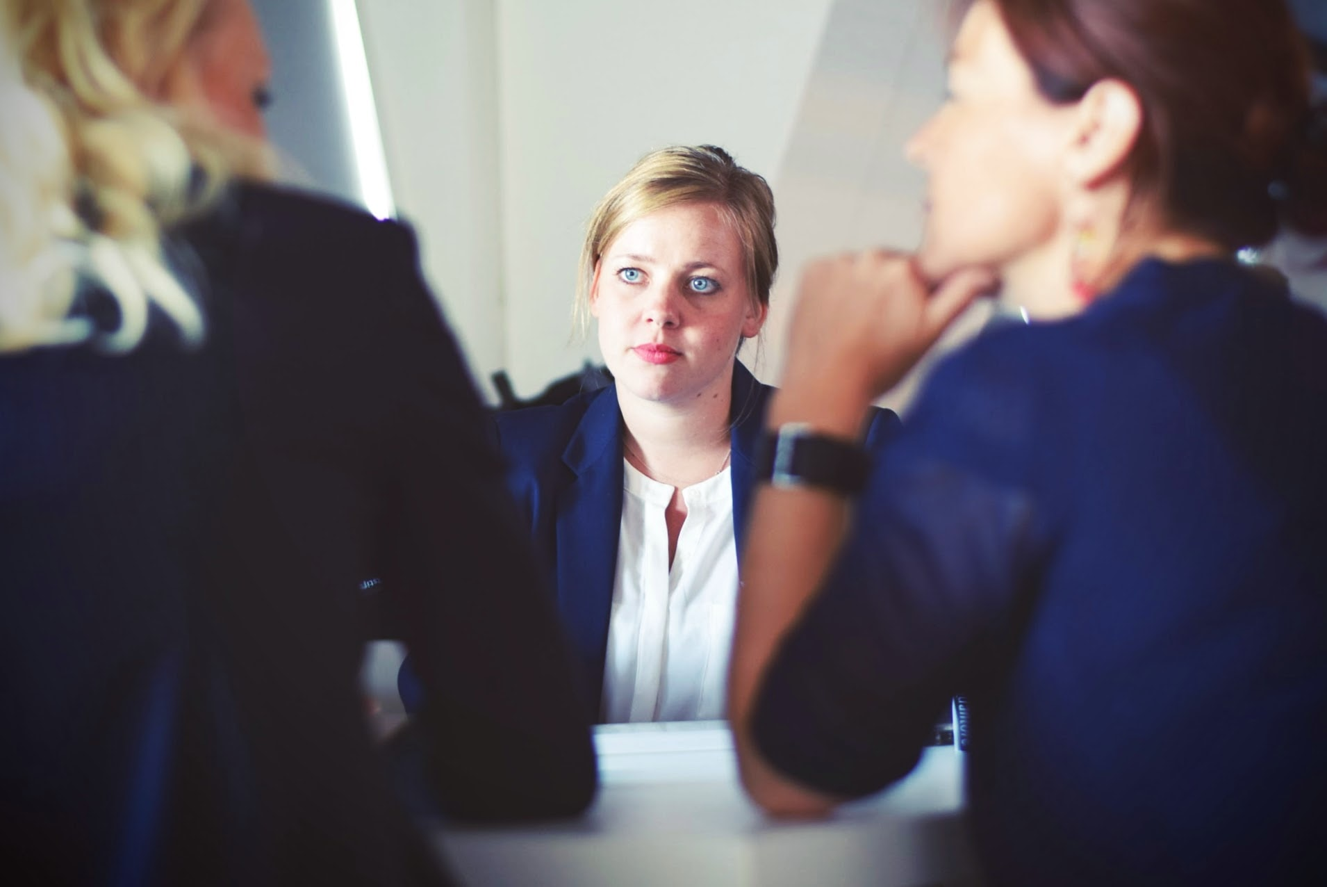 woman listening to two others in an interview
