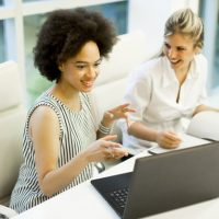 Happy african american and blonde  businesswomen with laptop computer in office