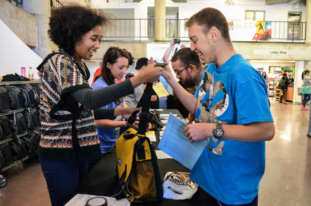 Mylisha Sexton, 21, a volunteer at Campus MovieFest, hands a bag of gear over to Jordan Kleinberg, 18, a freshman nursing major at SF State who is competing in this year's competition, Wednesday, Sept. 25, 2013 in the Cesar Chavez Student Center at SF State. Jordan is thinking about making his movie a comedy.  Photo by Amanda Peterson / Xpress