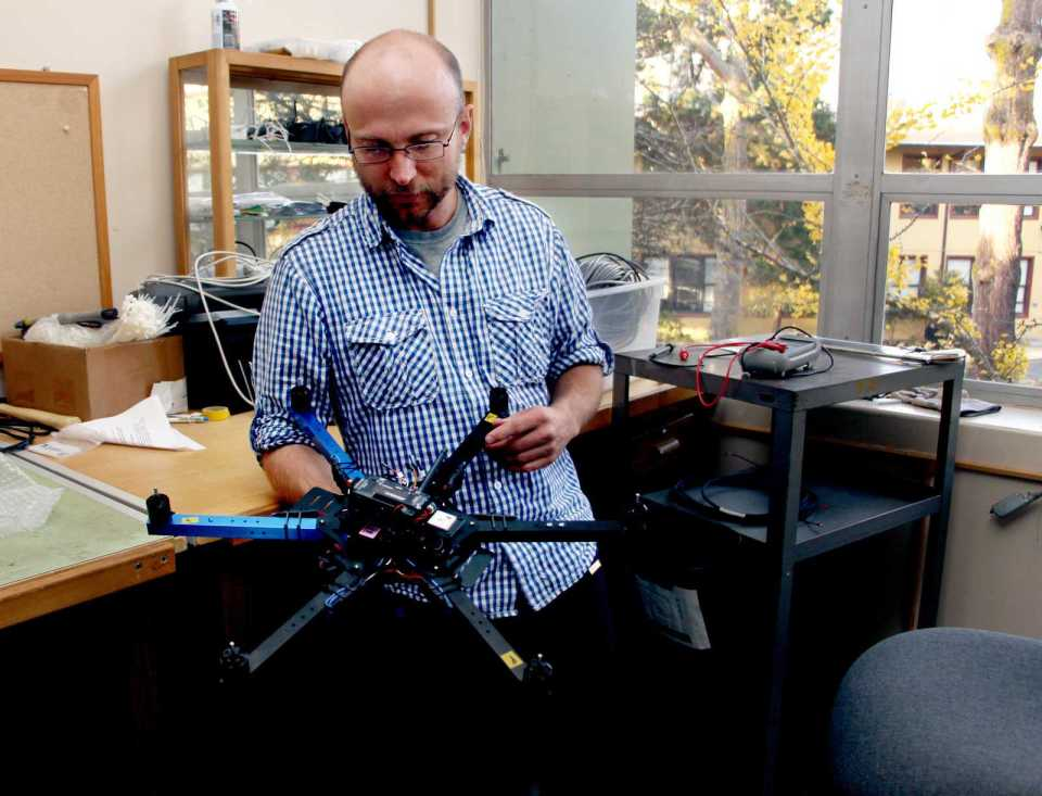 Peter Christian, a geographical information science graduate student, stands with the hexacopter being used to survey California landscapes. The hexacopter is a cheaper and safer way to get photos of California. Photo by Gavin McIntyre / Xpress