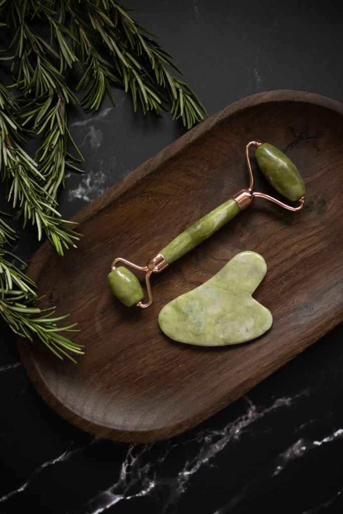 set of facial massage tools placed on wooden plate on black table