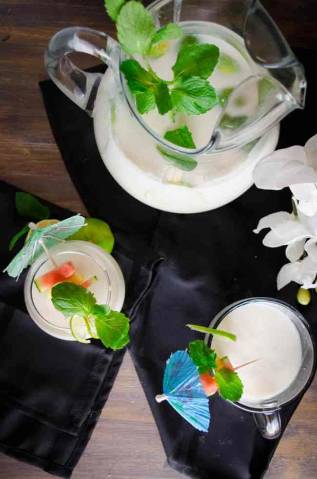 Crowd Pleasing Coconut Lime Mocktail fills glasses and a pitcher garnished with fruit and mint leaves.