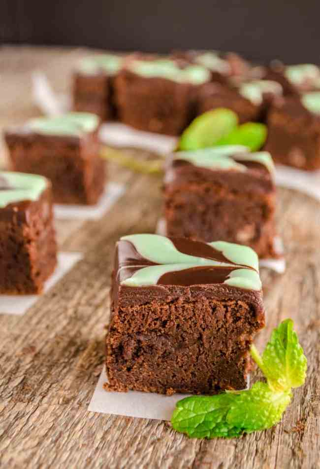 Fudgy Mint Brownies cut into individual squares on an old wooden table top.