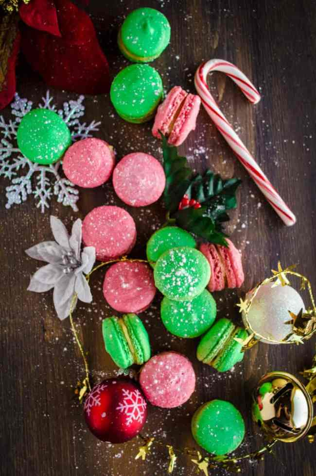 Red and Green Christmas Macarons spread out on a table with Christmas decorations.