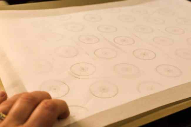 A printed macaron template placed on a cookie sheet used to make Christmas Macarons.