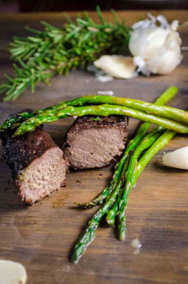 Grilled Elk Steak with Buttered Asparagus sliced to show the juicy meat inside. Asparagus sits to the side and on top of the steak.