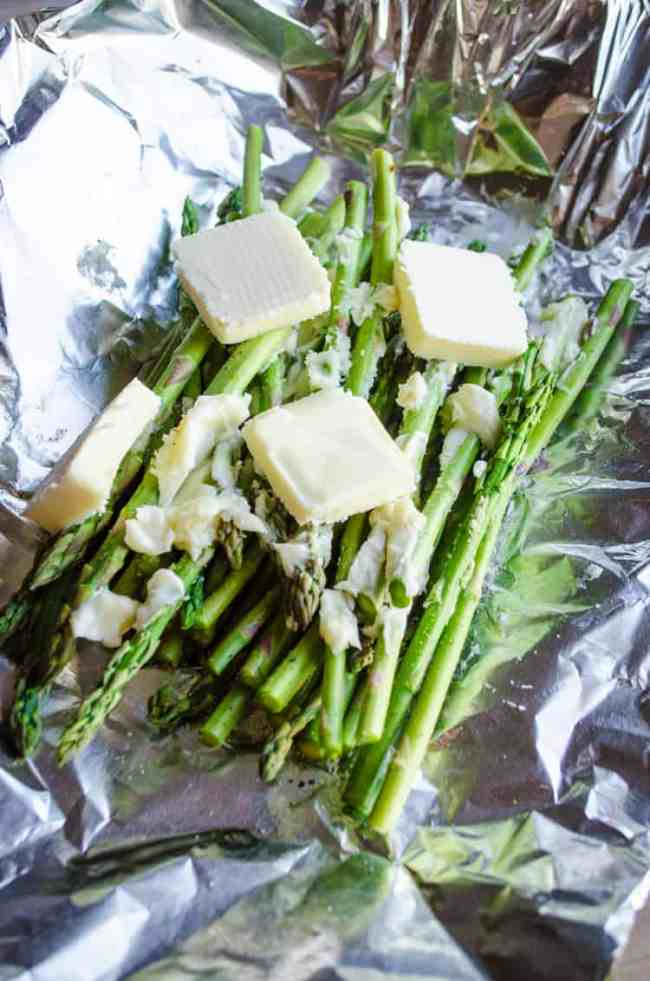 Asparagus stalks topped with pats of butter ready to be wrapped in foil for Grilled Elk Steak with Buttered Asparagus